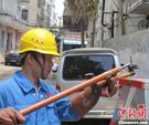 广东省中山市供电局抢修工人在海口市玉河维修更换供电设备